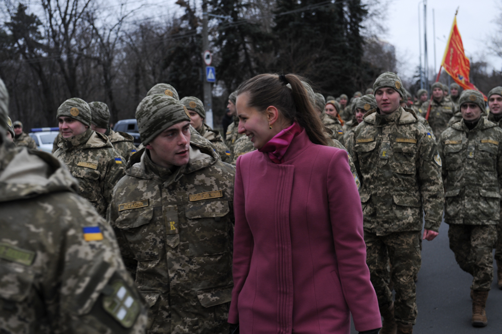 ODESSA, UKRAINE.  A Military Academy student marches down the street with a young woman beside him to a ceremony at the April 10 Monument where the student soldiers will be promoted to the rank of lieutenant on February 26, 2016.  With war raging in eastern Ukraine with Russian-backed separatists, more young men and women have enlisted and the popularity of military education has increased, including among civilians; the April 10 monument commemorates Soviet victory over the Nazi occupation in Odessa.