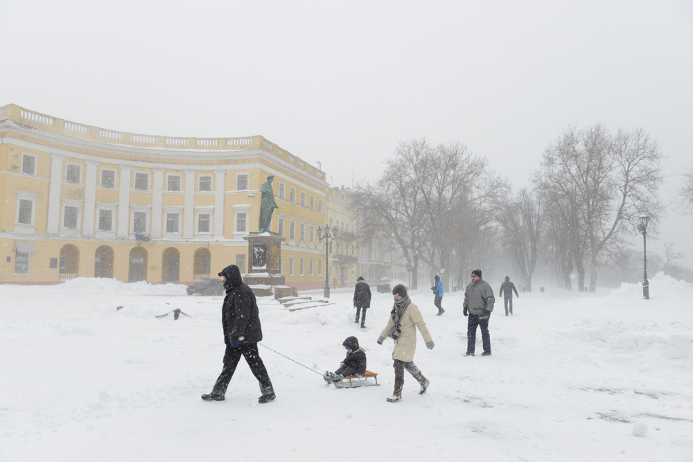 ODESSA, UKRAINE.  Pedestrians around a statue of the Duc de Richelieu at the top of the Potemkin steps in the snow on January 18, 2016.