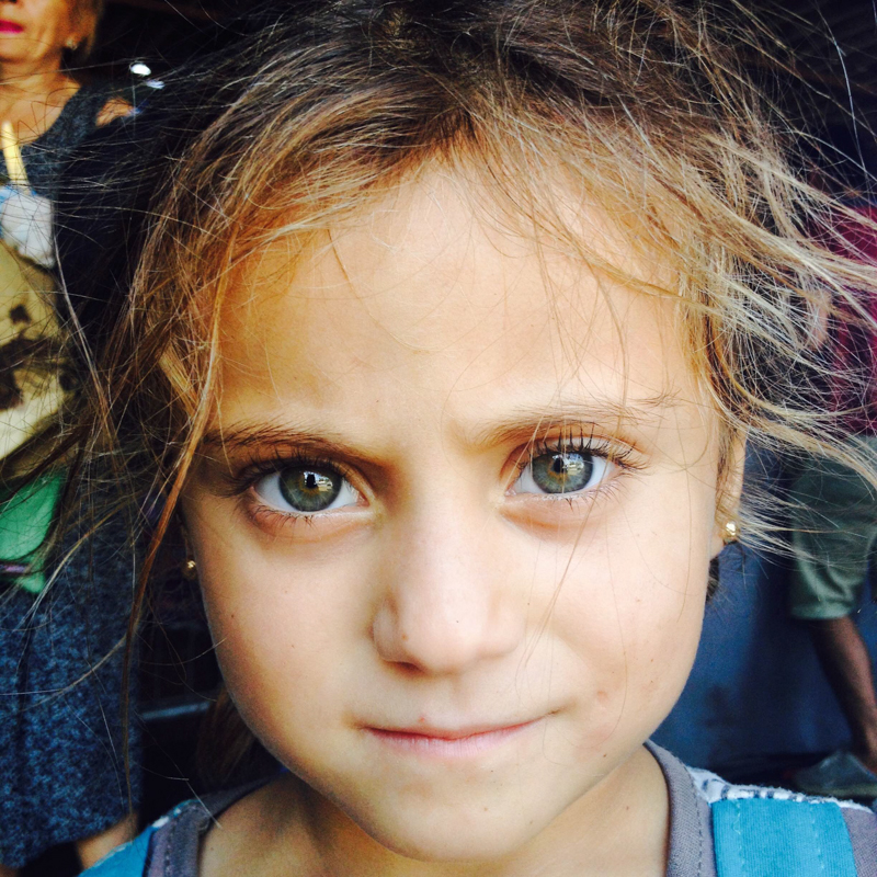 BELGRADE, SERBIA.  Rama Khatouf, 4, of Idlib, Syria at the Refugee Aid Serbia distribution center two blocks from the main train and bus stations on September 3, 2015. A tent city has sprung up in the park around Belgrade's main train and bus station over the course of the summer as tens of thousands travel through the Serbian capital from Syria, Iraq, Iran, Afghanistan and elsewhere en route to a better life in Europe, mainly Germany, Sweden and Switzerland; Khatouf was with her father and siblings receiving food and clothing aid.