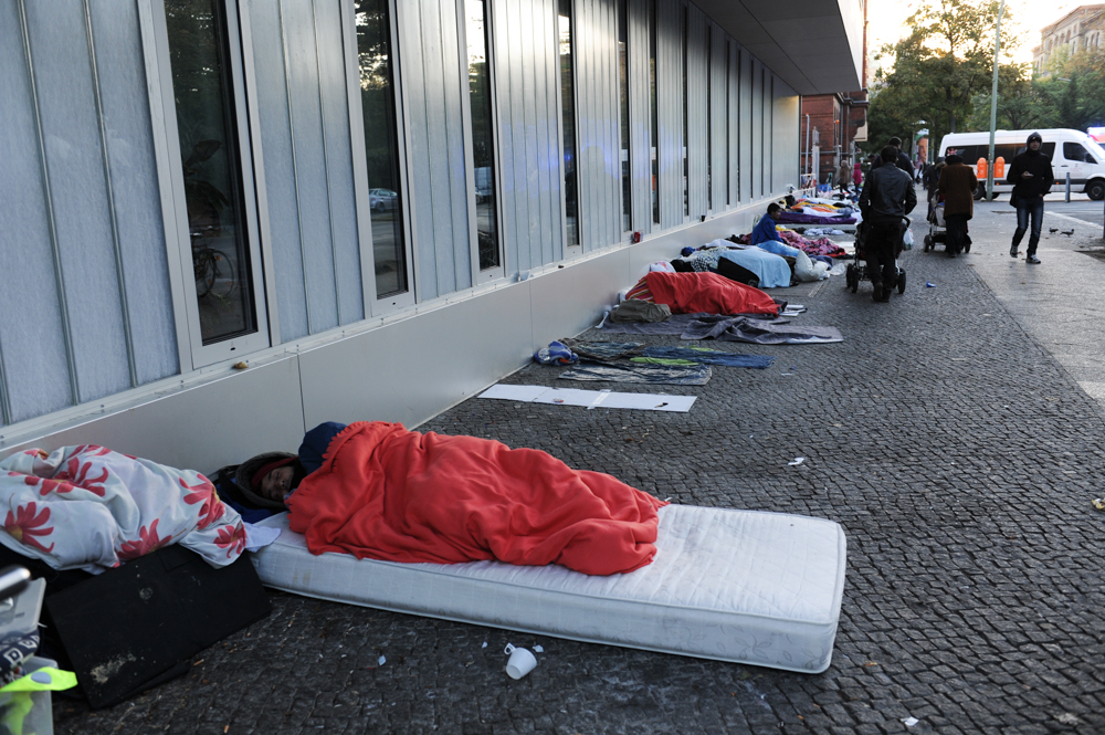 BERLIN, GERMANY.  Men from Afghanistan and Pakistan sleep on Turmstrasse (Turm Street) in front of the office of Landesamt für Gesundheit und Soziales (LaGeSo), the State Office for Health and Social Services, where refugees and asylum applicants arriving in Berlin must go to register their application for asylum, in the Moabit district on September 28, 2015.  German Chancellor Angela Merkel has said Germany will take 850,000 asylum applicants this year as many fleeing conflicts in Syria, Iraq, Afghanistan, Pakistan and elsewhere have migrated in mass to Europe through the Western Balkans seeking safety and a future.