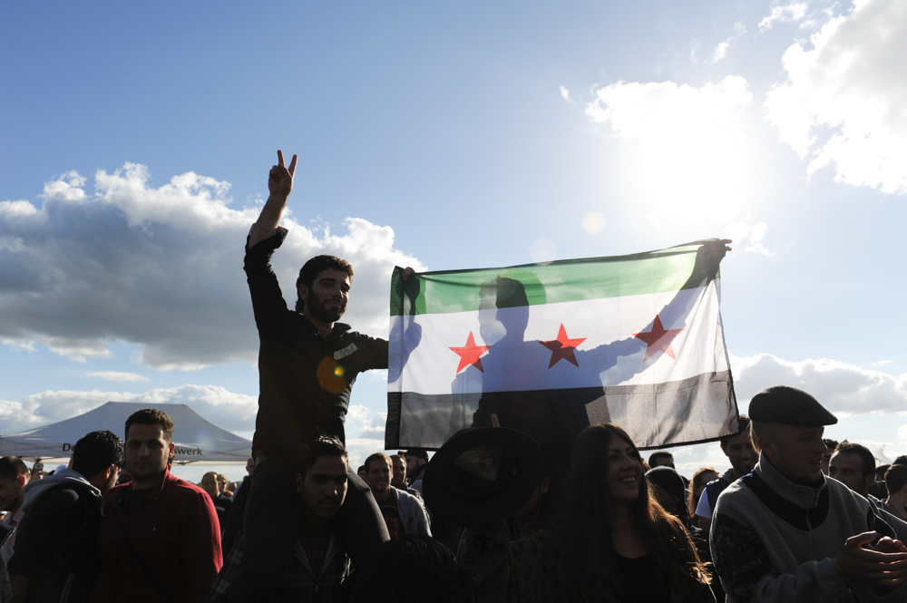 BERLIN, GERMANY.  Syrian refugees and others dance and sing and hoist up the Syrian flag at a {quote}Refugees Welcome{quote} picnic for refugees and asylum applicants arriving in large numbers in their country after having fled conflicts in the Middle East, Afghanistan and elsewhere at the Tempelhof Airport Park on September 27, 2015.  German Chancellor Angela Merkel has said the country is prepared to accept a historic 850,000 asylum applicants this year but has also sought to tighten its border control with Austria and other Schengen zone countries.
