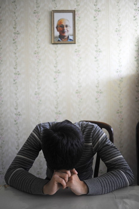 BAKU, AZERBAIJAN.  Asiman Tagili, 20, sits at the living room table under a portrait of his father, Rafiq Tagi, a journalist who was stabbed to death outside his home several years after an Iranian cleric, Grand Ayatollah Fazil Lankarani, placed a fatwa against him for writings deemed critical of Islam and the Iranian state, on March 20, 2012.