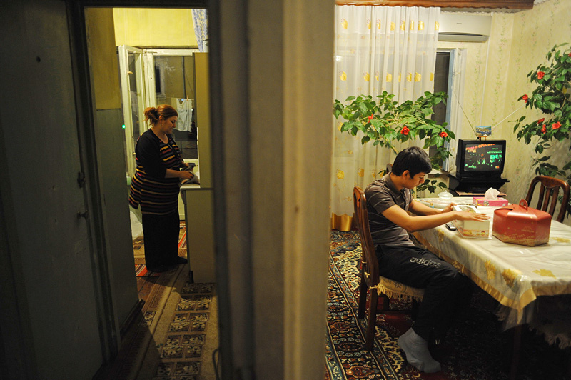 BAKU, AZERBAIJAN.  (L-r) Maila Tagiyeva, 48, stands in the kitchen as her son, Asiman Tagili, 20, prepares the living room table for desert to celebrate Maila's 48th birthday, the first without her husband, Rafiq Tagi, a journalist who was stabbed to death outside his home several years after an Iranian cleric, Grand Ayatollah Fazil Lankarani, placed a fatwa against him for writings deemed critical of Islam and the Iranian state, on May 3, 2012.