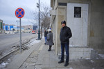BAKU, AZERBAIJAN.  Asiman Tagili, 20, waits for the bus near his family's apartment underneath a portrait of an Azeri martyr of the war in Nagorno-Karabakh to take his final university exam at Khazar University on January 30, 2012.