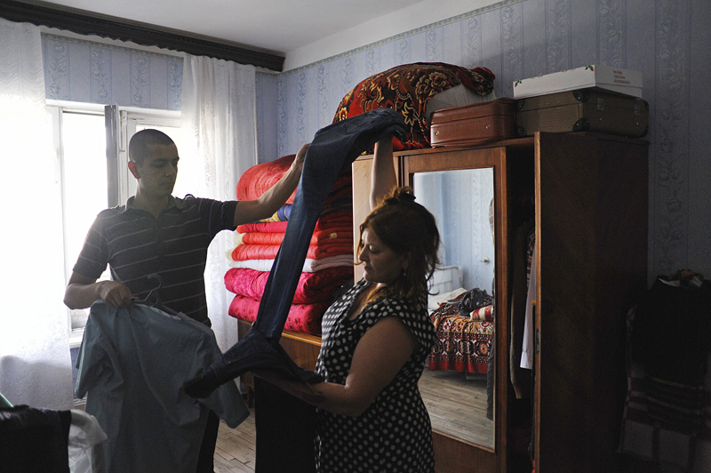 BAKU, AZERBAIJAN.  (L-r) Asiman Tagili, 20, takes a pair of pants from his mother, Maila Tagiyeva, 48, that she picked out for him in the family bedroom in the morning before Asiman takes his military oath and receives his marching orders on July 5, 2012.