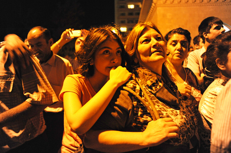 BAKU, AZERBAIJAN.  (L-r) Gamar Tagili, 15, embraces her mother, Maila Tagiyeva, 48, at the railyard as they are surrounded by the family members of other military conscripts after Asiman Tagili, 20, boarded a train to Shemkir in western Azerbaijan to fulfill his military service obligations on July 5, 2012.