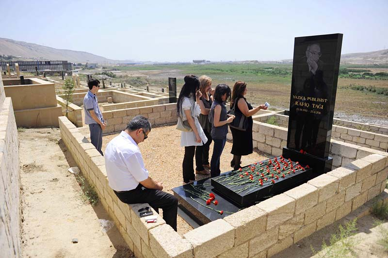 BAKU, AZERBAIJAN.  (Second from the right) Gamar Tagili, 15 and her widowed mother (far right), Maila Tagiyeva, 48, cry over the grave of Rafiq Tagi on his birthday alongside other members of the extended family including his sister, Yeguna (third from right), and her daughter, Ayten (third from left), at a cemetery on the outskirts of Baku on August 5, 2012.