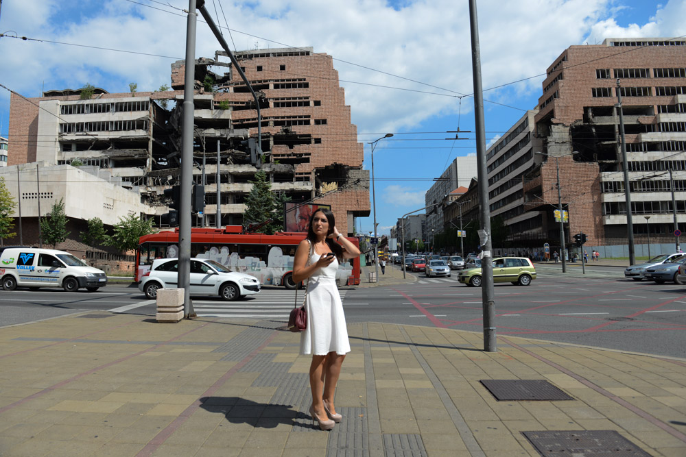 BELGRADE, SERBIA.  A woman stands in front of the former Serbian Ministry of Defense (at left), formerly the Yugoslav Ministry of Defense, and the Army Headquarters (at right), which were hit by NATO bombs in 1999 during the conflict with Kosovo under former Serbian leader Slobodan Milosevic, which have been left since as a morbid reminder of sorts of Serbia's recent past on Kneza Milosa on June 29, 2015.  Part of the Army Headquarters building remains in use.