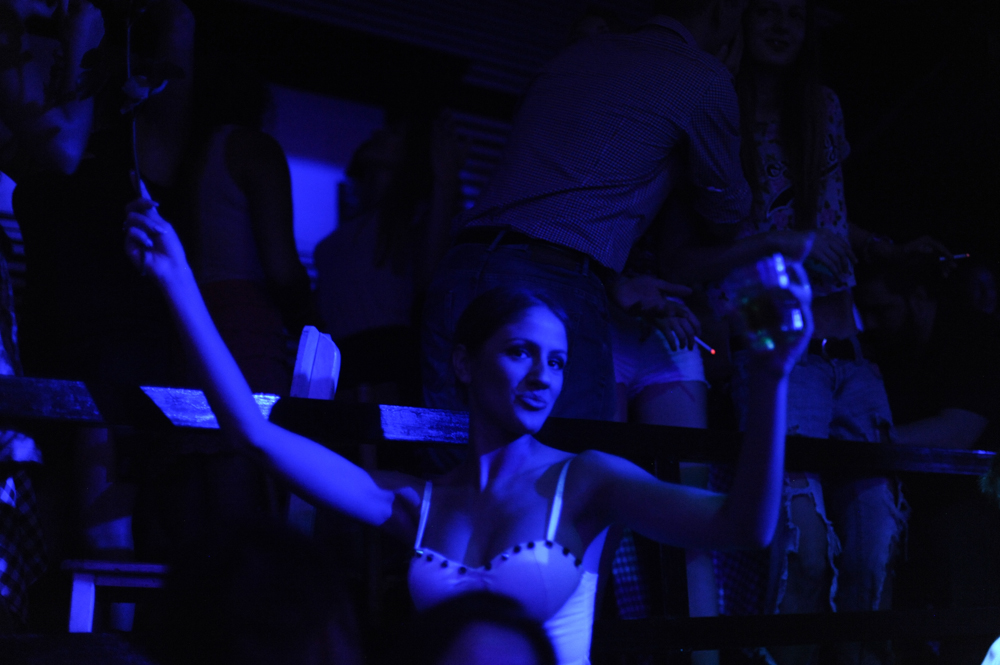 BELGRADE, SERBIA.  A clubgoer at Bard, a nightclub on a splav or barge on the Danube River, dances to fast-paced turbofolk hits by Dara Bubamara on the main dance floor of the club on July 8, 2015.  Dara Bubamara's career extends back to 1989 when she got her start on television singing songs by Lepa Brena.