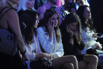 ISTANBUL, TURKEY.  Women are seen talking on their cell phones in the front row before the start of the Erol Albayrak Spring/Summer 2013 fashion show at Istanbul Fashion Week on October 11, 2012.