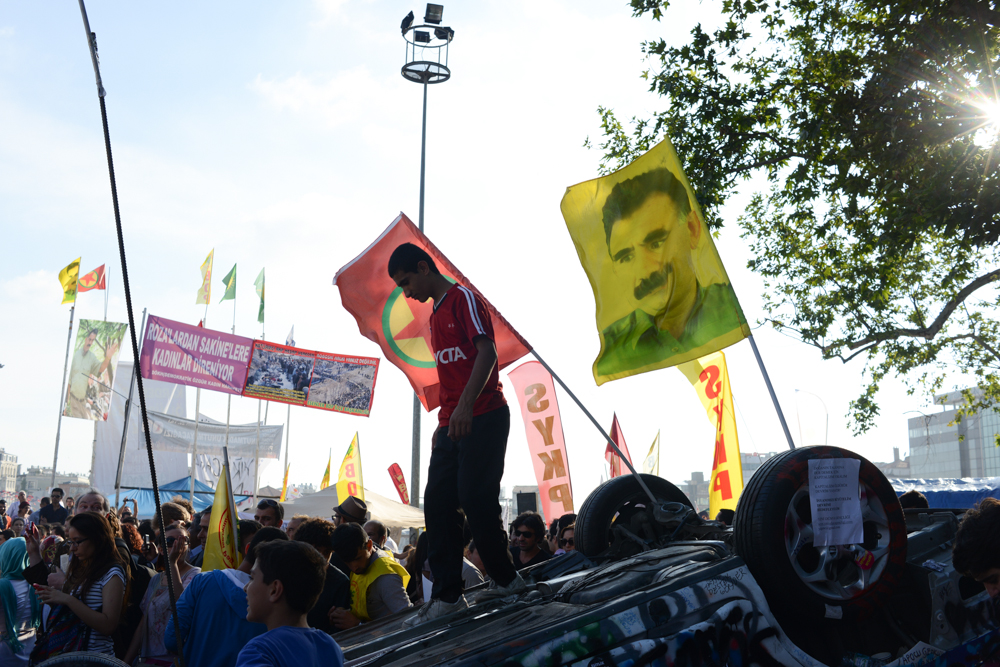 ISTANBUL, TURKEY.  Flags bearing Abdullah Ocalan, the jailed PKK leader, and the Kurdish national flag are seen in the middle of Taksim Square on an overturned police vehicle during a protest of the Prime Minister Recep Tayyip Erdogan and his policies a week after demonstrators forced police to withdraw from the square leading to a carnival-like sit-in on June 8, 2013. A week of protests led to police being barricaded out of and withdrawing from Istanbul's Taksim Square as it transforms increasingly into a free zone; the crisis, which began over construction of a park and plans to reconstruct Ottoman barracks and a shopping mall, has evolved into Turkey's biggest political crisis in decades as Turks express frustration with the current AK Party, Justice and Development Party and Prime Minister Recep Tayyip Erdogan.