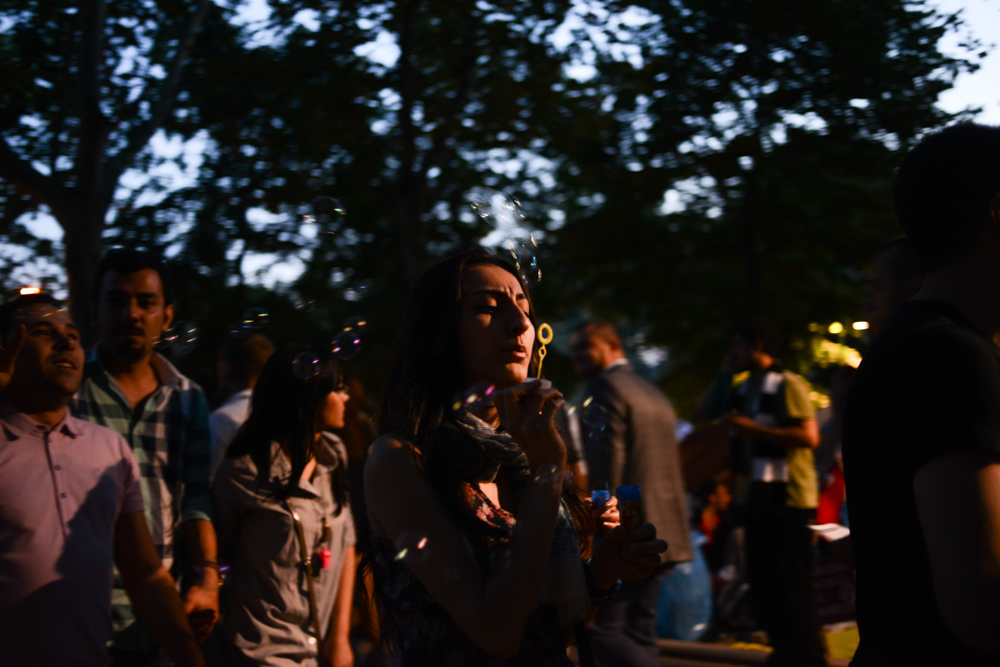 ISTANBUL, TURKEY.  A young woman blows bubbles in Gezi Park adjacent to Taksim Square where ongoing protests against the Prime Minister Recep Tayyip Erdogan and his policies a week after demonstrators forced police to withdraw from the square have lead to a carnival-like sit-in on June 8, 2013. A week of protests led to police being barricaded out of and withdrawing from Istanbul's Taksim Square as it transforms increasingly into a free zone; the crisis, which began over construction of a park and plans to reconstruct Ottoman barracks and a shopping mall, has evolved into Turkey's biggest political crisis in decades as Turks express frustration with the current AK Party, Justice and Development Party and Prime Minister Recep Tayyip Erdogan.