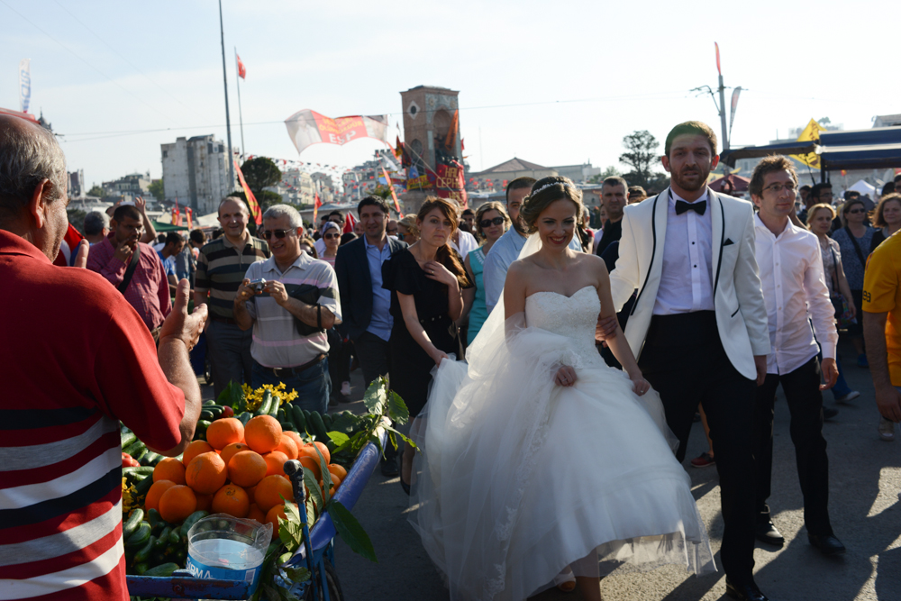 ISTANBUL, TURKEY.  A bride and groom promenade in Taksim Square in protest of the Prime Minister Recep Tayyip Erdogan and his policies a week after demonstrators forced police to withdraw from the square leading to a carnival-like sit-in on June 8, 2013. A week of protests led to police being barricaded out of and withdrawing from Istanbul's Taksim Square as it transforms increasingly into a free zone; the crisis, which began over construction of a park and plans to reconstruct Ottoman barracks and a shopping mall, has evolved into Turkey's biggest political crisis in decades as Turks express frustration with the current AK Party, Justice and Development Party and Prime Minister Recep Tayyip Erdogan.