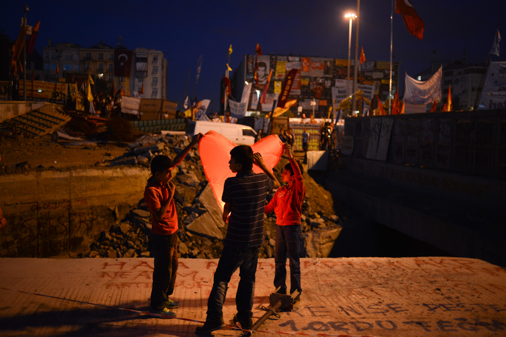 ISTANBUL, TURKEY.  Turkish children light a paper lantern at a protest in Taksim Square after a week of protests led to police being barricaded out of and withdrawing from the square as it transforms increasingly into a free, carnival-like zone in Istanbul, Turkey on June 6, 2013. The crisis which began over construction of a park and plans to reconstruct Ottoman barracks and a shopping mall has evolved into Turkey's biggest political crisis in decades as Turks express frustration with the current AK Party, Justice and Development Party, and Prime Minister Recep Tayyip Erdogan.