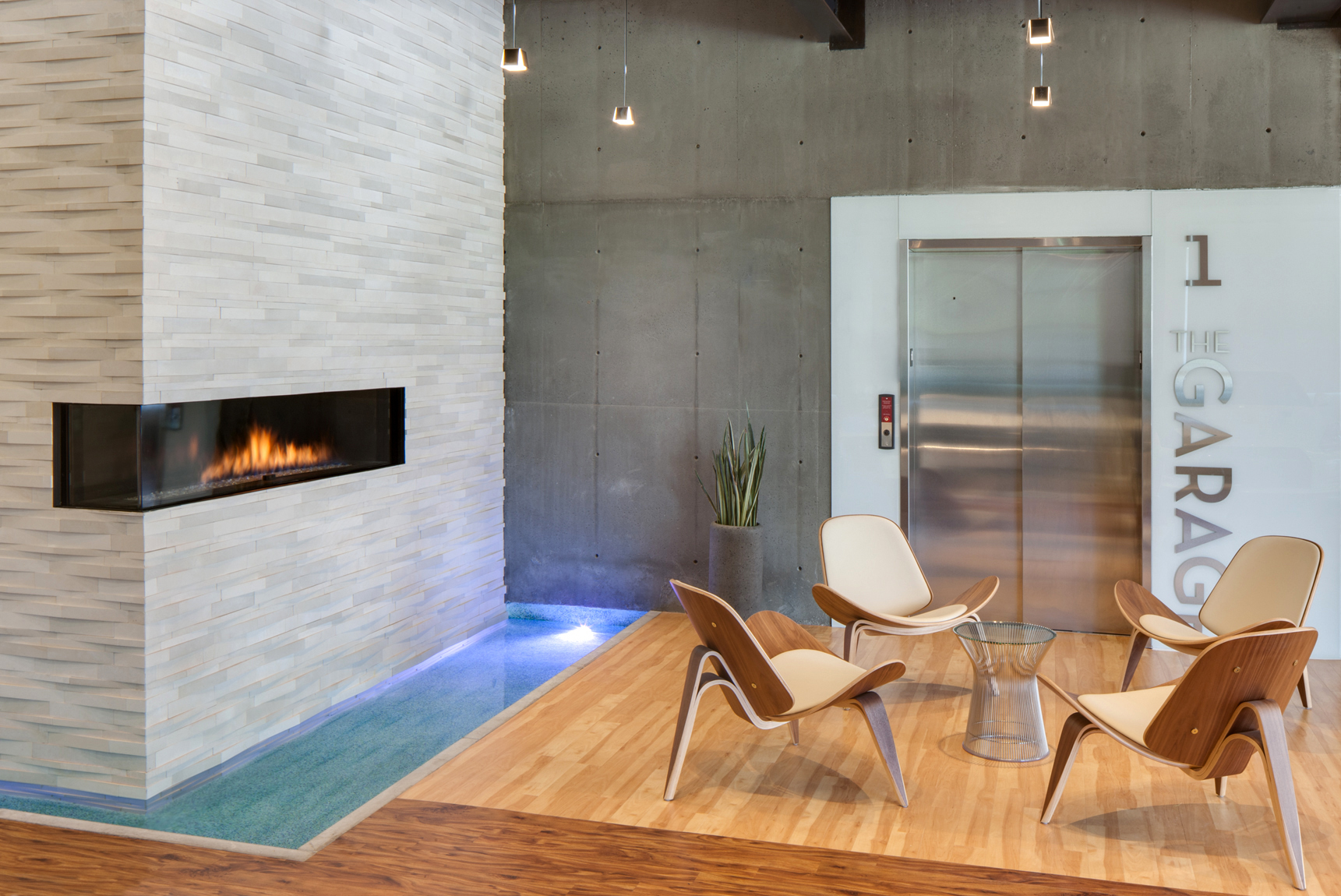 Modern office space with gas fire place, wood furniture, a water feature and a stainless steel elevator.Private Office Studio for Method StudiosArchitectural Photography by: Paul Richer / RICHER IMAGES