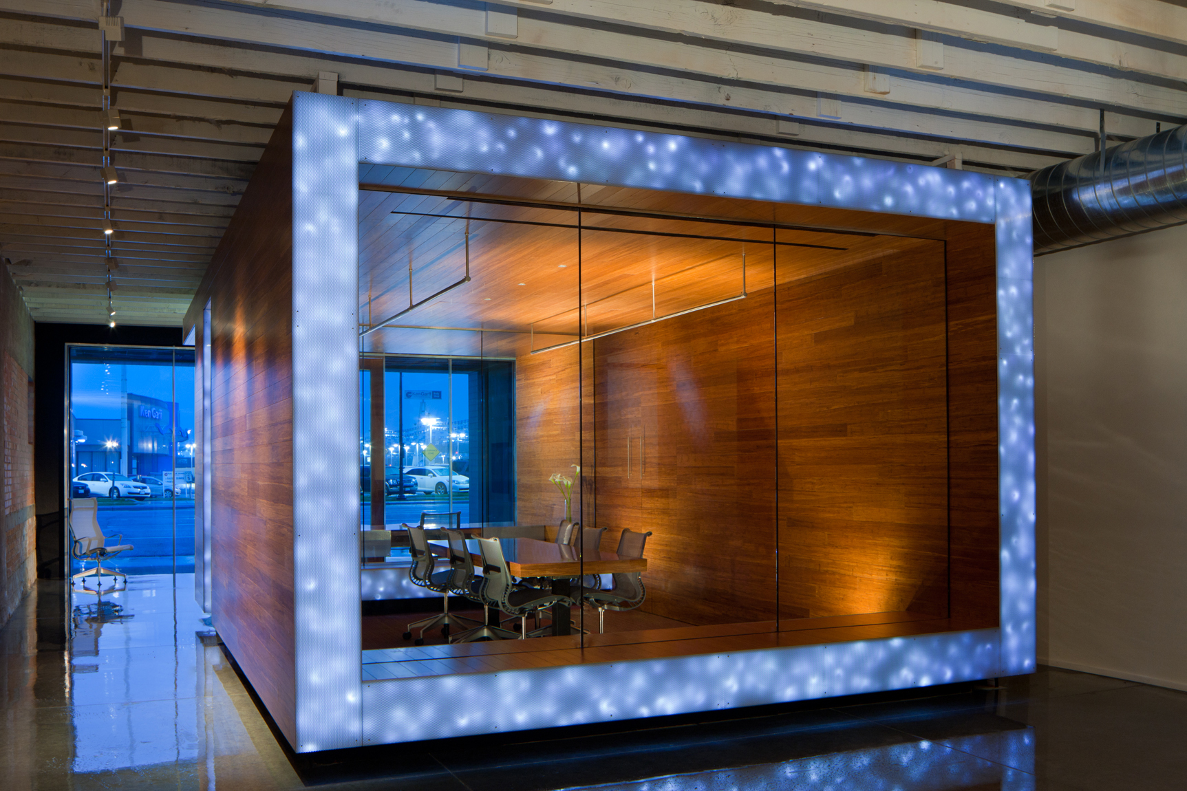 View of office conference room made of warm wod and glass with LED lights. Shiny concrete floors and blue, dusk windows.Architectural Photography by: Paul Richer / RICHER IMAGES