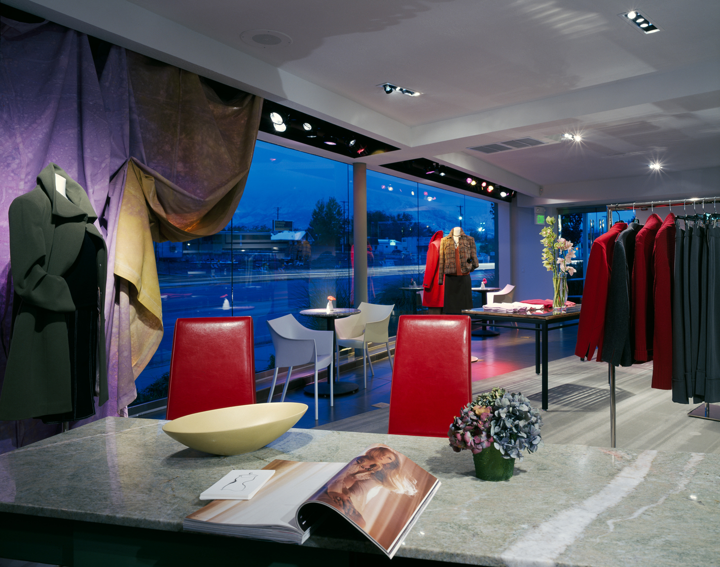 Interior view looking itowards the street in an  upscale clothing boutique at dusk with cool, blue exterior and warm interiors.Architectural Photography by: Paul Richer / RICHER IMAGES