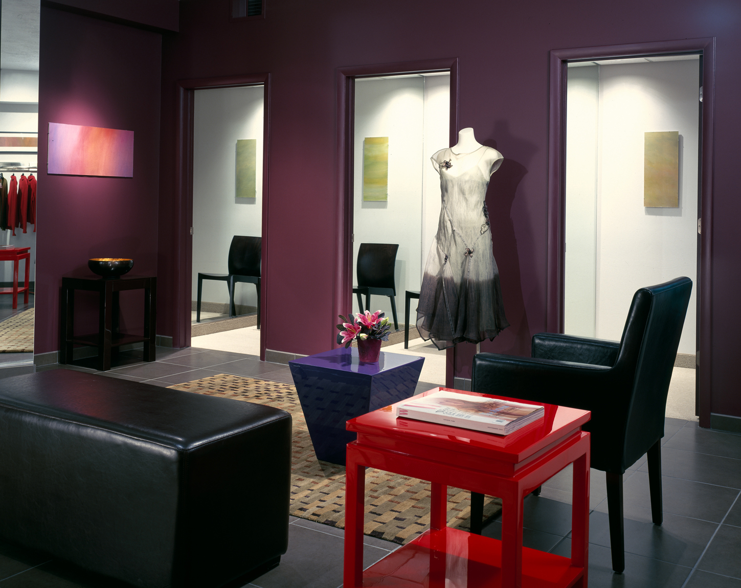 Interior view towards changing rooms in an upscale clothing boutique. Black leather furnishings are framed by maroon walls and the centerpiece features a bright red table.Architectural Photography by: Paul Richer / RICHER IMAGES