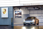 Exterior view looking in to a service bay at Porsche of Salt Lake dealership. The entrance framing a beautiful, silver Porsche 911. Architectural Photography by: Paul Richer / RICHER IMAGES