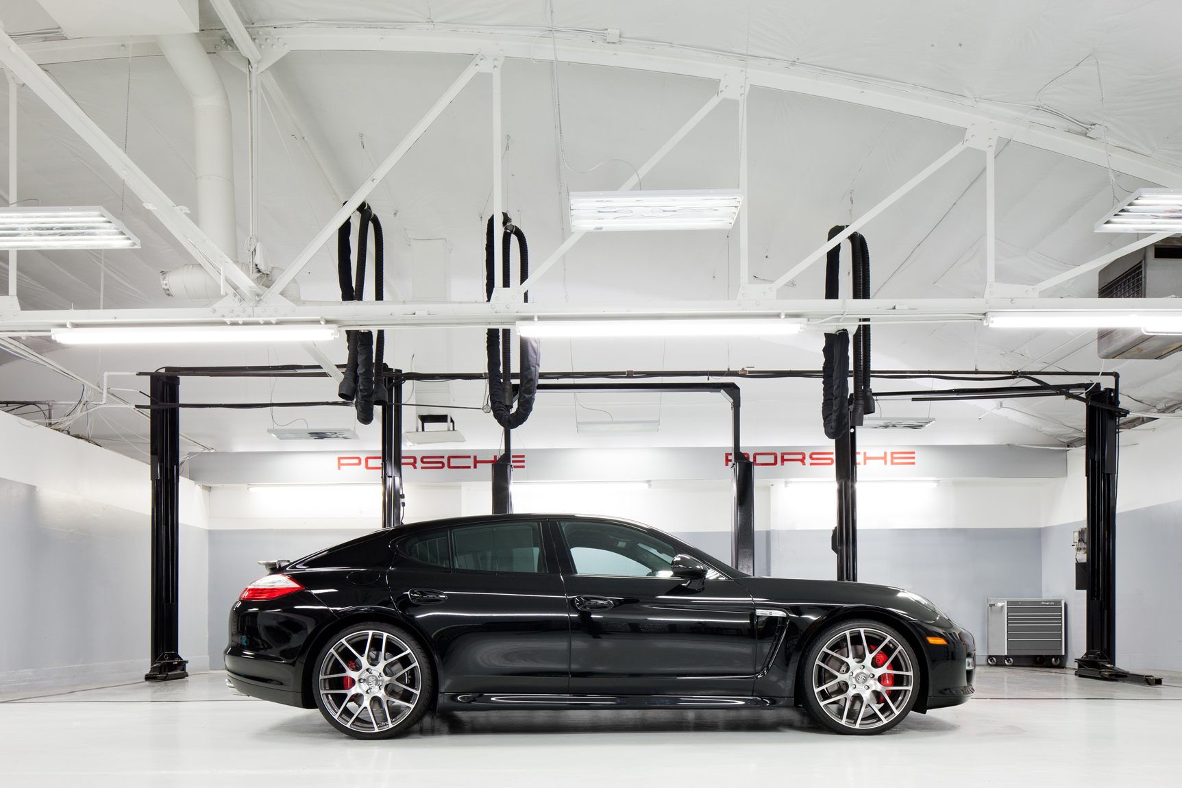 Interior high key, view of  black  Porsche Panamera in a service bay with white and gray walls.  Architectural Photography by: Paul Richer / RICHER IMAGES