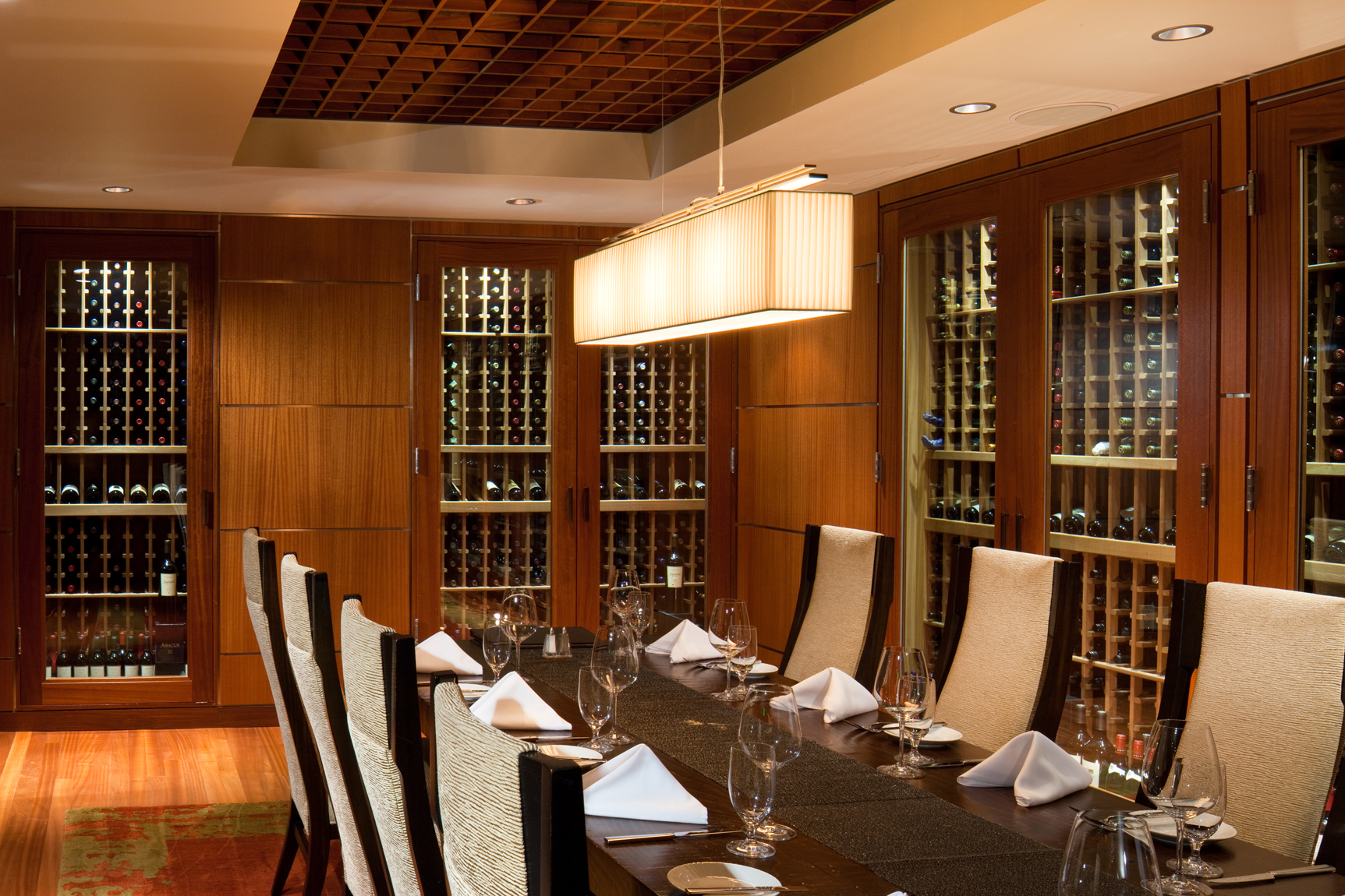 View of private dining room in a casino with wood panel walls and wine cabinets.Hospitality, resort, casino, photography in Scottsdale, AZ.