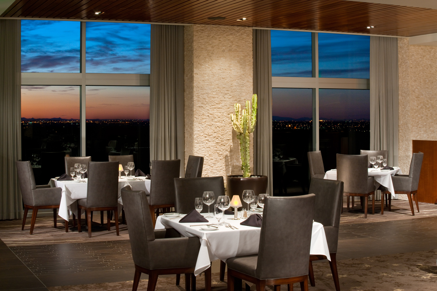Twilight view of dining room with nicely lit furnishings and dusk, blue windows. Hospitality, resort, casino, photography in Scottsdale, AZ.