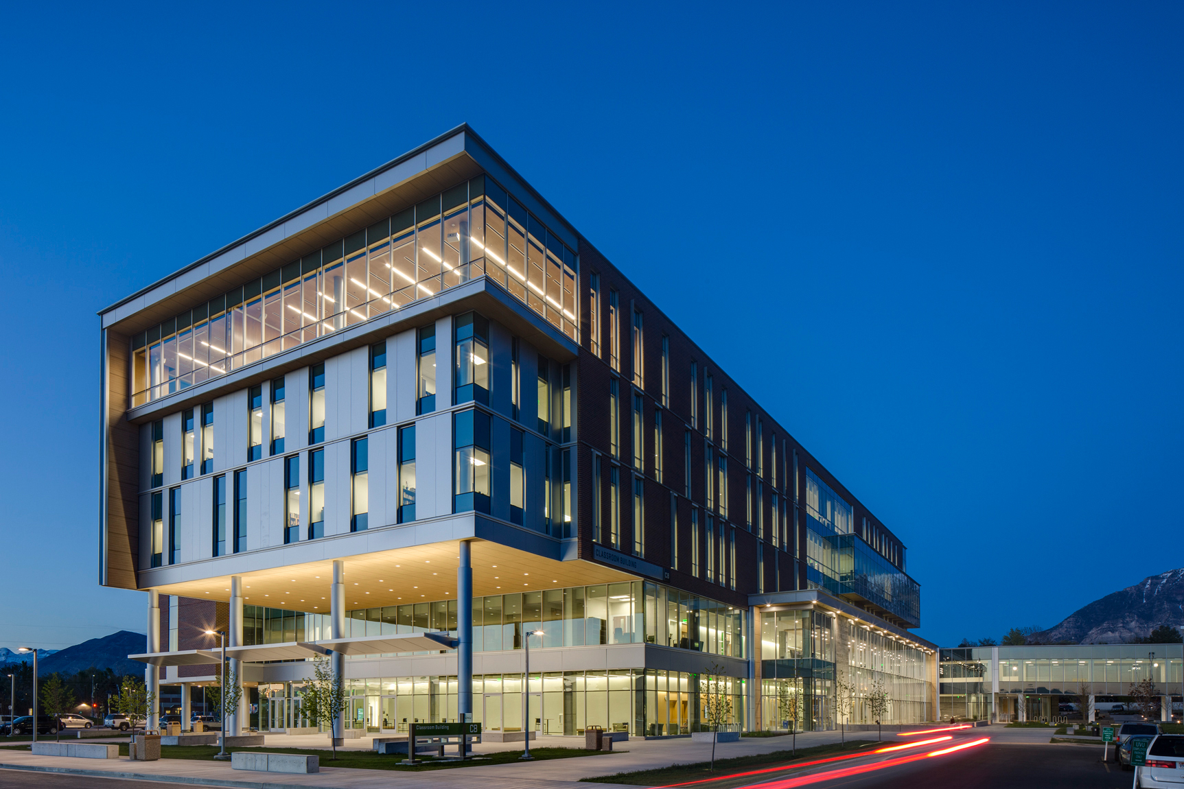 Exterior view at dusk of modern looking college classroom building as car drives thogh with red tail light tracers.Architectural Photography by: Paul Richer / RICHER IMAGES