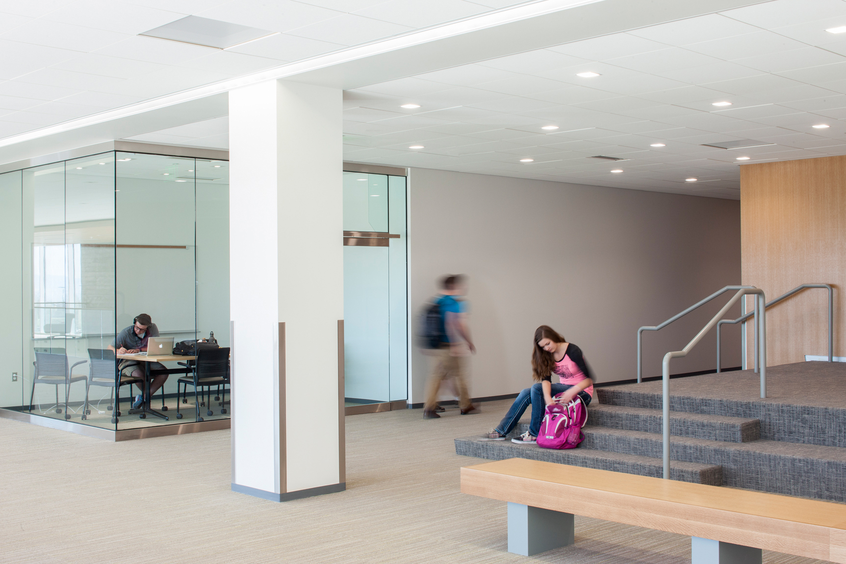 Interior view of college classroom building with student activity and transparent study rooms.