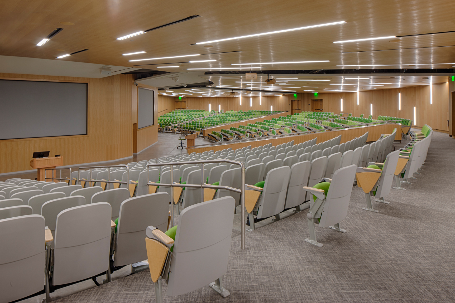 Interior view of college lecture hall with green seating which can be partitioned.Architectural Photography by: Paul Richer / RICHER IMAGES
