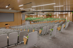 Interior view of college lecture hall with green seating which can be partitioned.