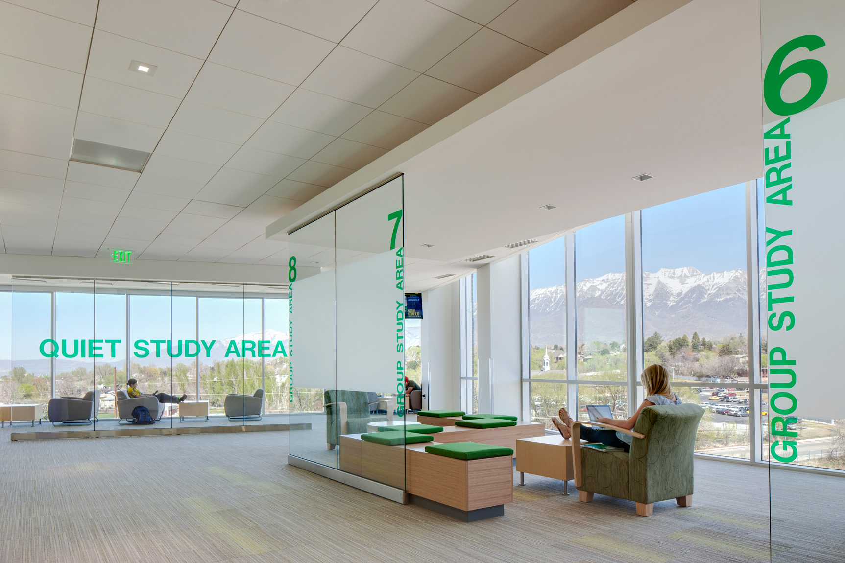 Students studying in quite area with tall glass windows and mountain views ant Utah State University.