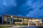 Exterior view of transparent college building at dusk with illuminated art in front and stormy blue skies.