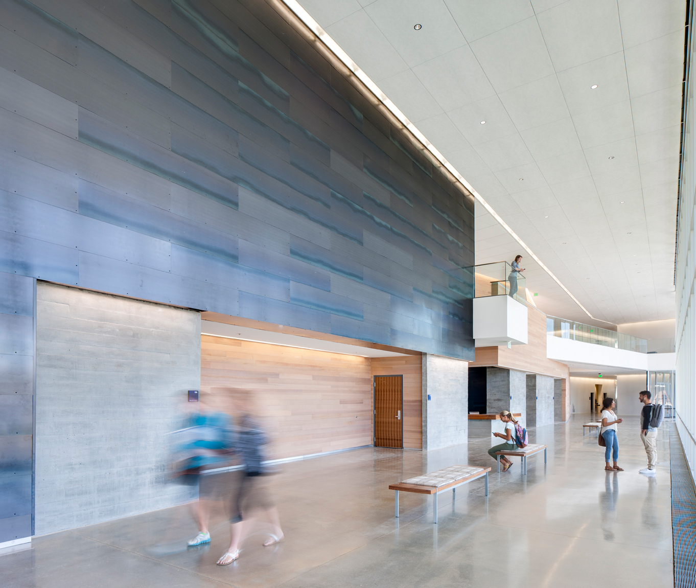 Photo os college students occupying main common space of a new academic building with copper cladding, concrete floors, wood panneling and natural day light.