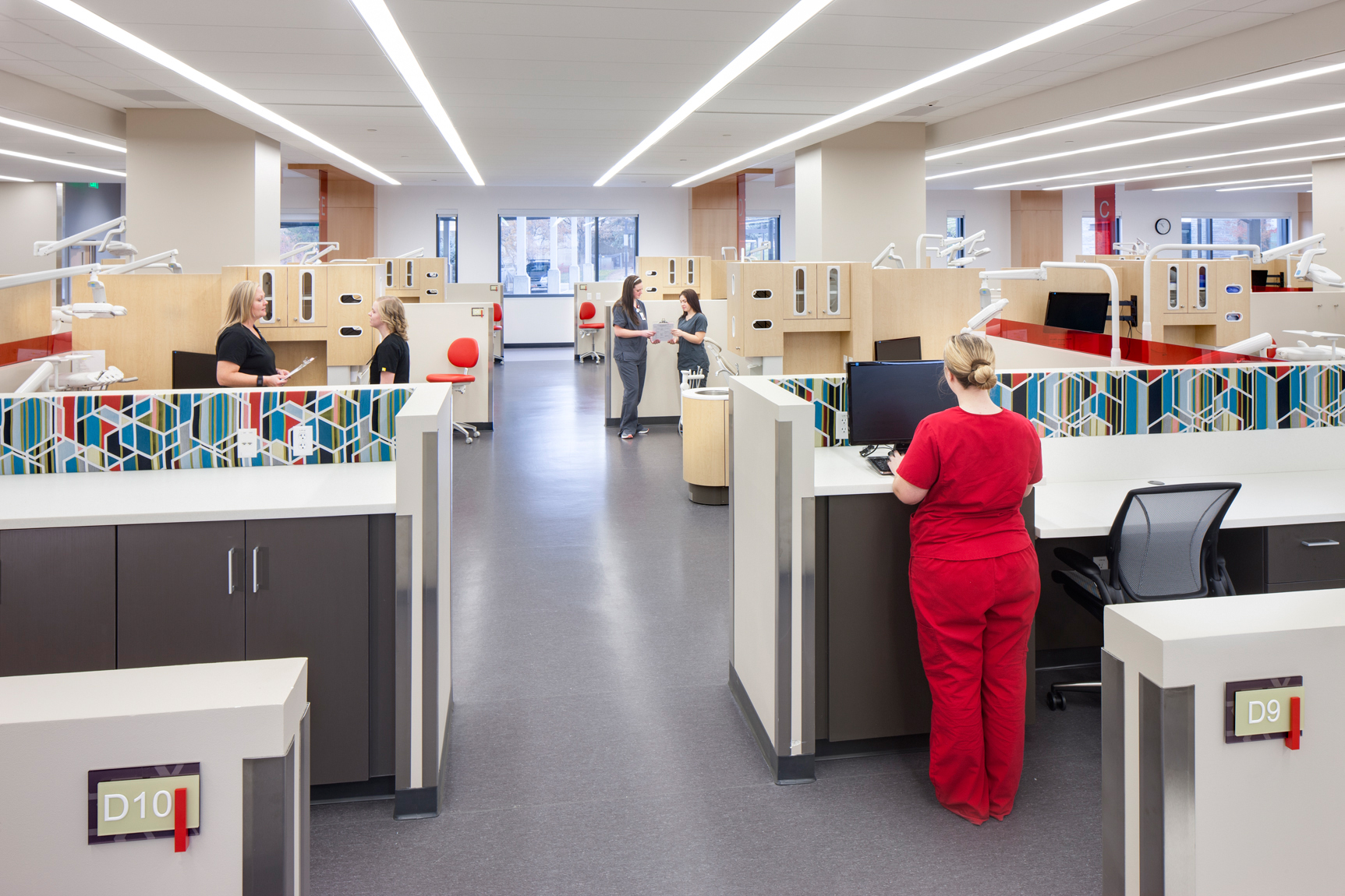 General Practice lab at the U of U Oral Health & Sciences Building with rows of dental stations and a student in proper dental attire.
