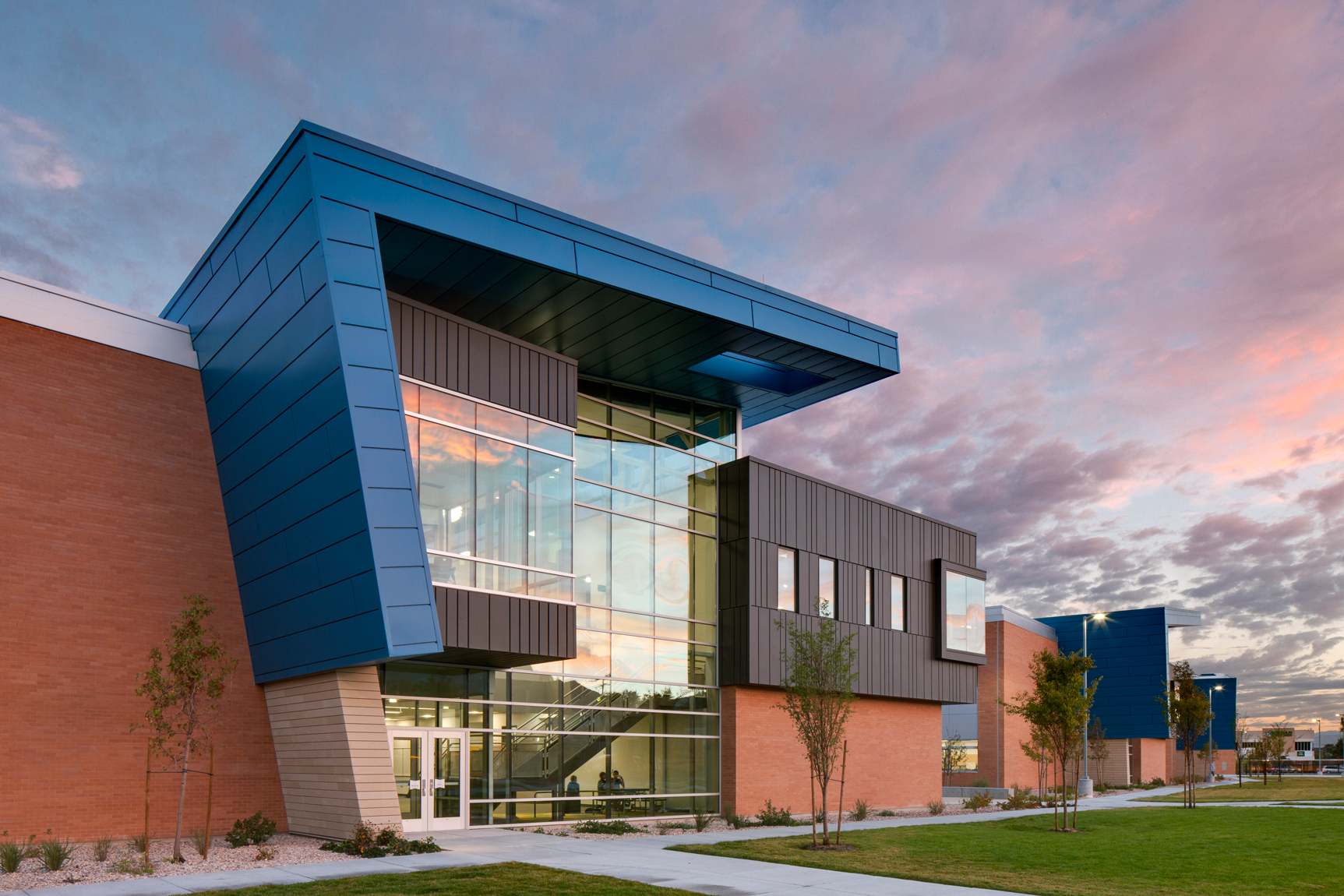Exterior view of classroom wing at sunrise at Mt. Jordan Middle School in Sandy Utah for MHTN Architects / Hogan & Associates. These wings feature metal cladding and overhangs of blue metal. Architectural Photography by Paul Richer / RICHER IMAGES