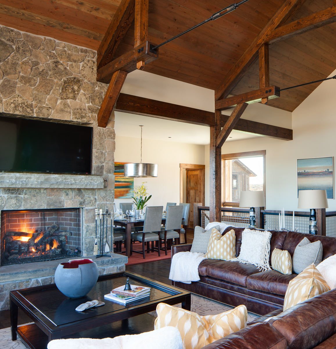 View of main living room in a mountain rustic home in eastern Idaho. The dining area can be seen in the back of the photo and in the forgrround we see a lit fireplace with a coffee table and a leather couc=h.