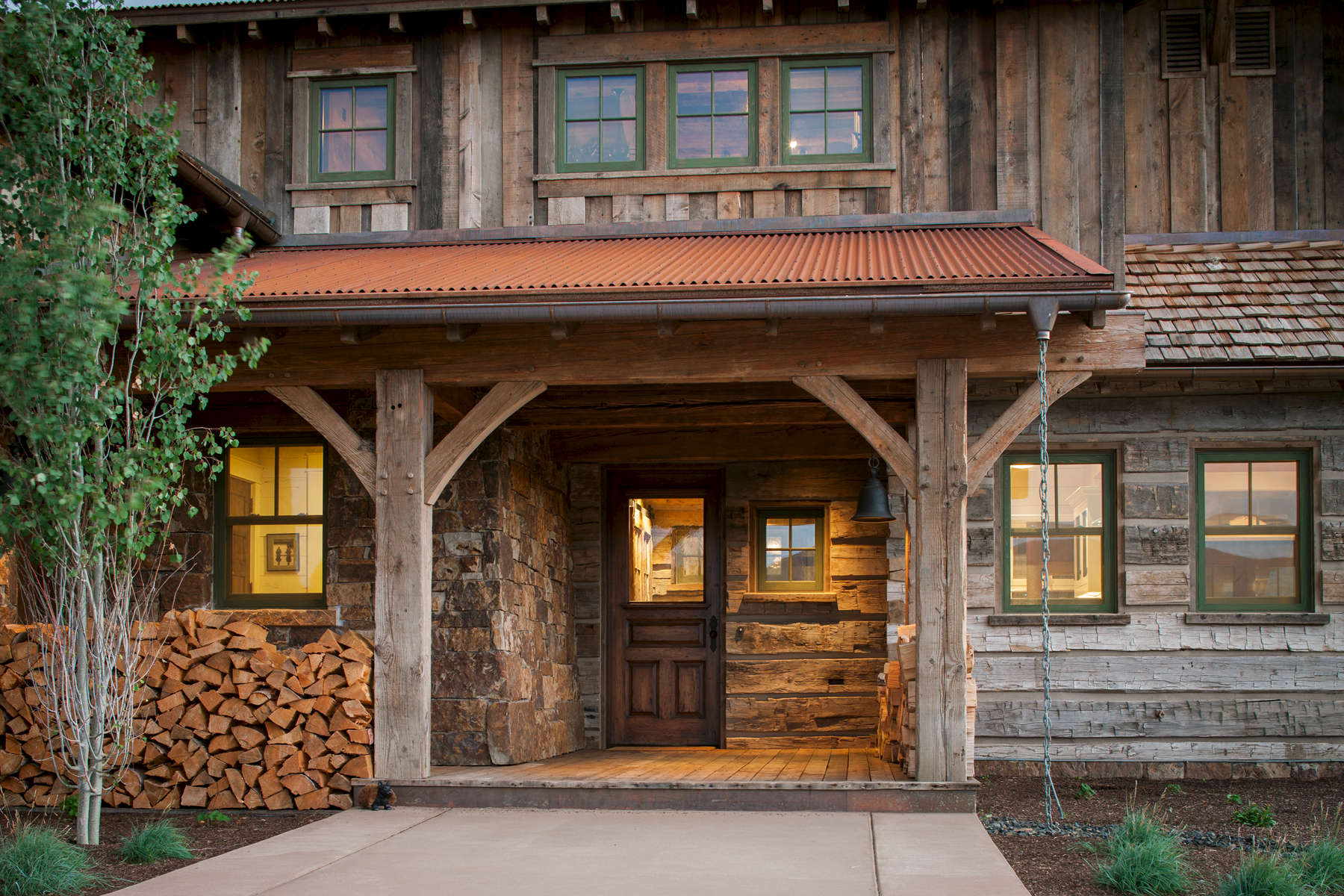 This view of the main entrance to a Private Residence near Park City, UT. for Line 8 Design.shows warm glowing windows and pleanty of rustic and reclaimed timber.Architectural Photography by: Paul Richer / RICHER IMAGES.