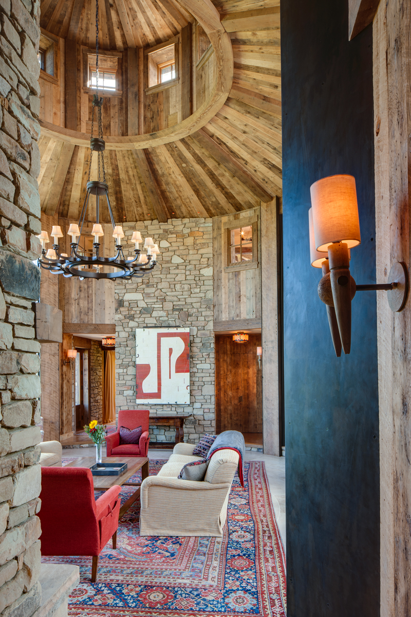This is an interior view of a private residence in Jackson, Wyoming's Shooting Star development. The image shows the stone work of the fire place and features a raw wood rotunda in the center of the ceiling. There is a rustic chandeleir hanging from the rotunda and the room has nice antique carpeting.Architectural Photography by: Paul Richer / RICHER IMAGES