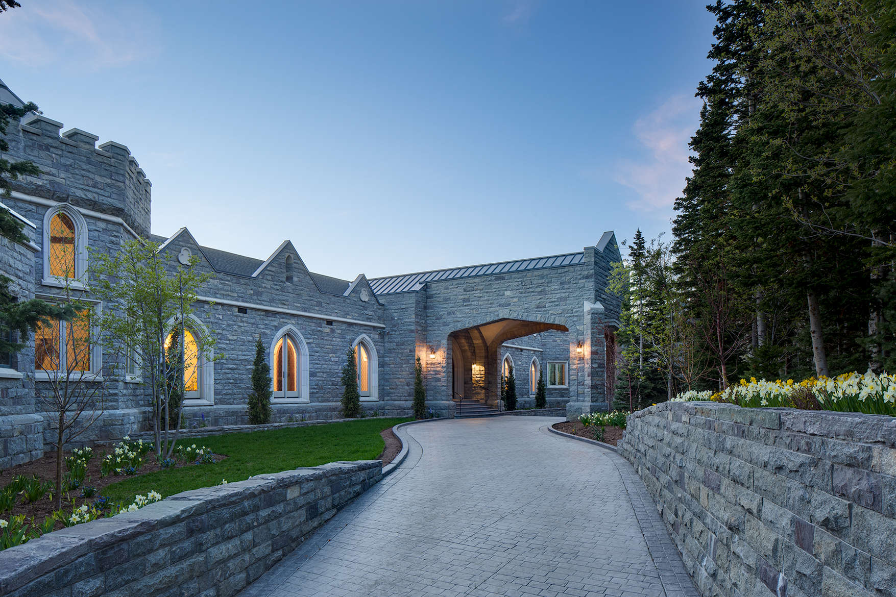 Exterior view at dusk looking up stone walled drive way of a Scott manor house in Park City, UT with glowing windows.