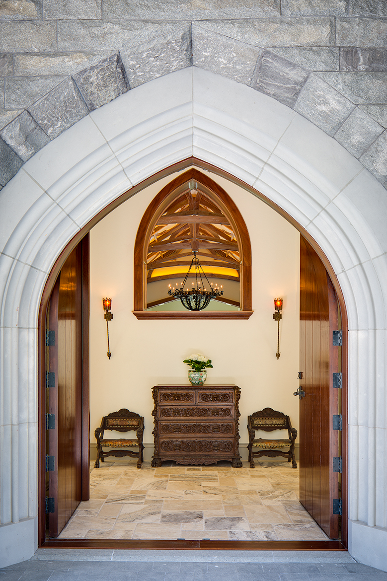 View through main entrance of a Scottish stle manor house. Heavy oak doors, stone floors and a peak in to the living room with an orante wood ceiling