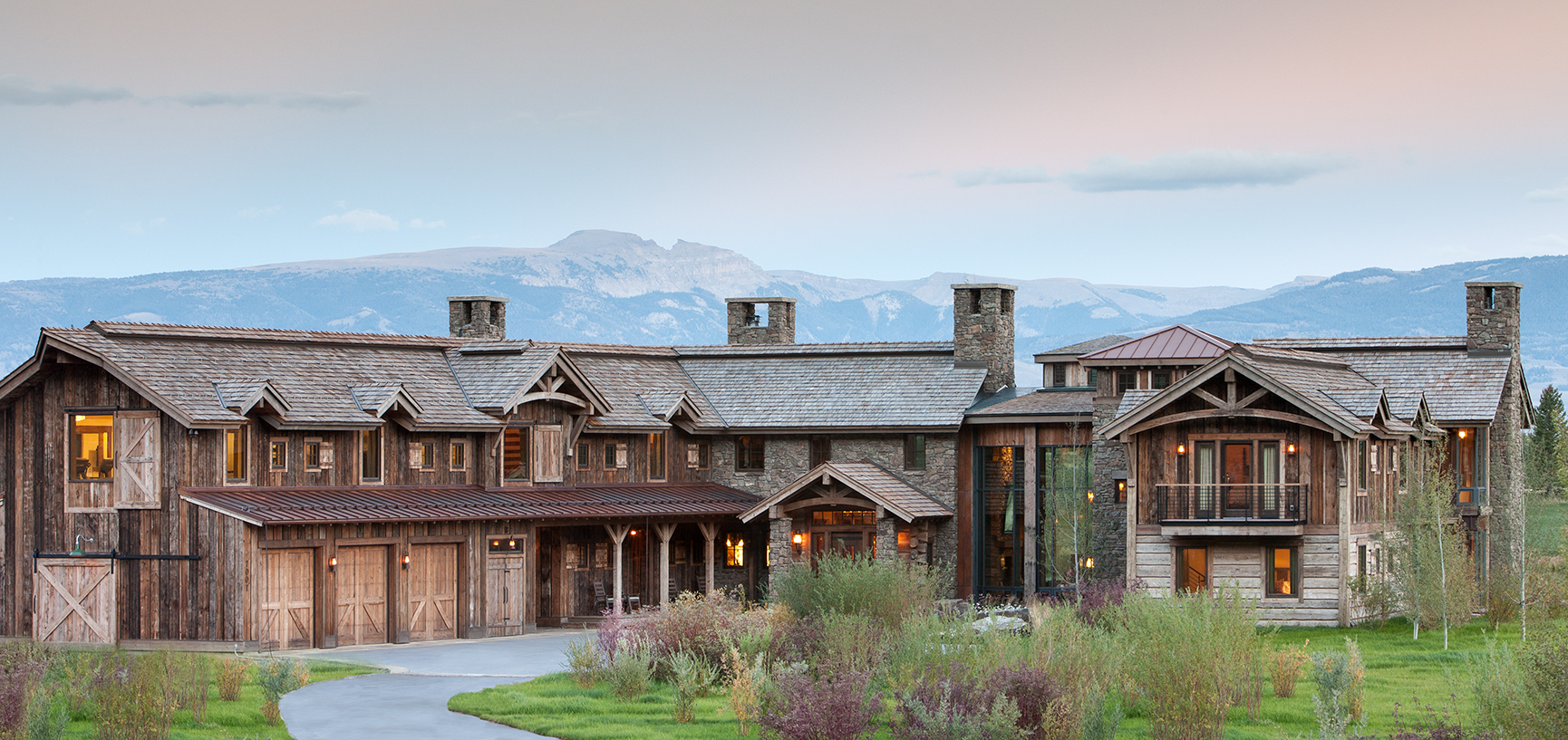 This is an exterior elevation photo of a private residence at Shooting Star in Jackson Wyoming. The house is large and rustic with a raw or reclaimed timber lok to it and has a view of Jackson's Sleeping Indian behind.Architectural Photography by: Paul Richer / RICHER IMAGES