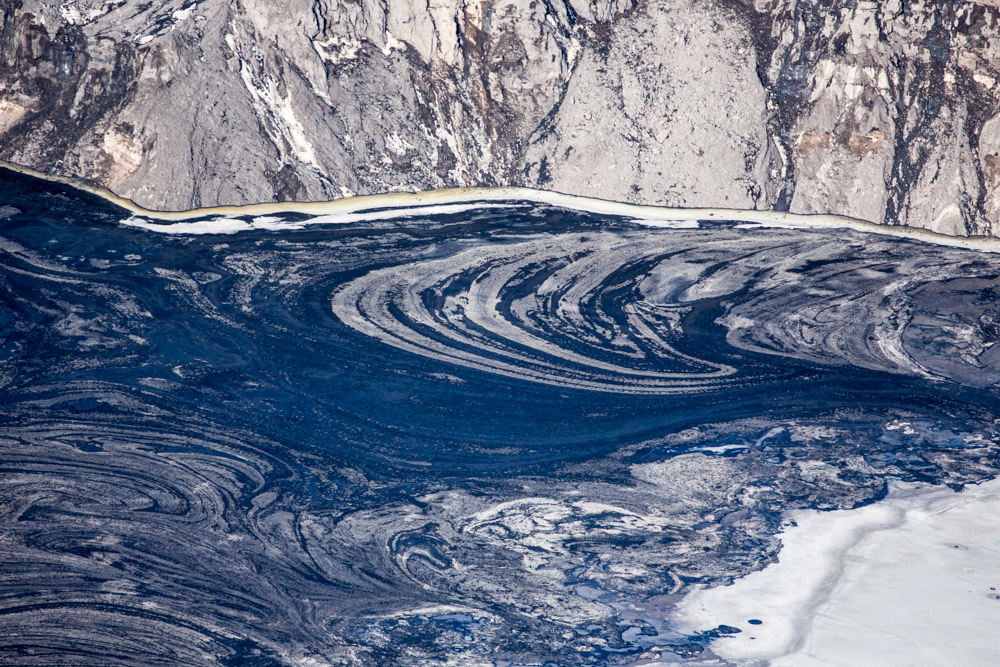 Oil Swirls and Ice Float Atop Tailing Pond, Syncrude Mildred Lake, Alberta, Canada 2014File Ref. #140407-0414