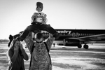 Sgt. Wesley Newton throws his son, Noah, 4, on his shoulders as his wife Anne, all of Lincoln, Neb. look on Wednesday, Dec. 7, 2011 at the Nebraska National Guard Air Base in Lincoln, Neb.