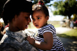 Pfc. Virniqua Watkins of Sparta, Ga. consoles her teary-eyed daughter Harmony, 1, after a deployment ceremony Friday, Oct. 15, 2010 at Ft. Gordon, Ga. About 100 troops from A Company, 345th Military Intelligence Battalion will deploy to Baghdad, Iraq tomorrow morning at 8:00 a.m. but will head first to training, for six weeks, at Ft. Bragg, N.C. Their mission, the first unit to deploy since the end of combat operations announced last month, will serve as the Corps Analytical Augmentation Element for United States Forces Iraq located at Camp Victory for 12 months. {quote}Am I going to miss her?{quote} Watkins said. {quote}Just look at her.{quote}