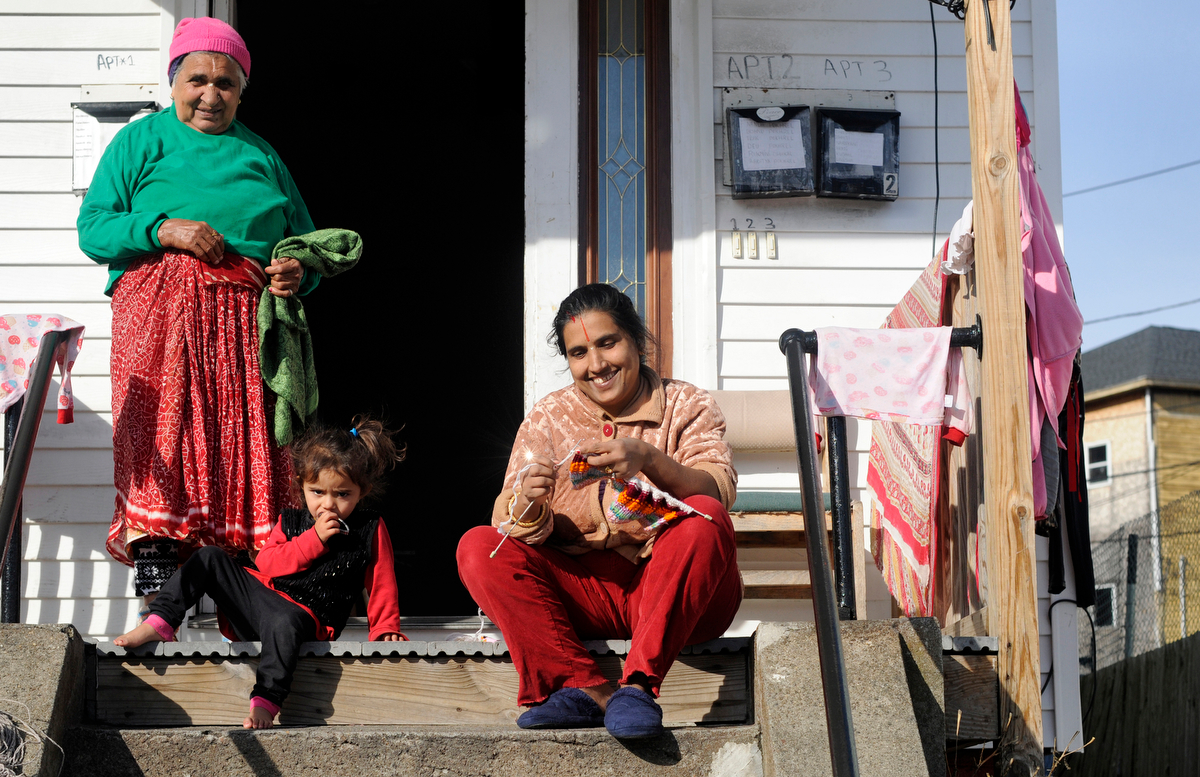 Tika Gsimersey knits on her Winfield Street stoop soaking up the morning sun with her daughter, Seikisya, 2, and Mon Gsimersey, left, on Thursday, Dec. 4, 2014.