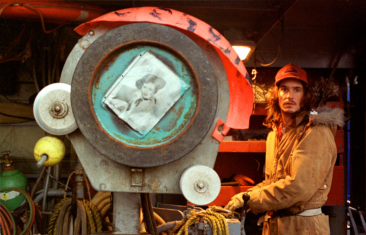 "Aboard the deck of the F/V Big Valley, crewmen Eric Grumpke runs the hydrolics next to the crab coiler which bears a picture of Barbara Stanwyck, star of the television show that is the boat's namesake, while the boat is in King Cove, Alaska preparing for the red king crab season on October 29, 1993. Grumpke drove the crane that shifted gear and equipment on deck. In the winter, arctic nights last 18 hours. The sun barely comes above the horizon before it begins its retreat back below the surface. Everyone's eyes adjust to the long winter nights, creating a glassy-eyed crew. The ""Aleutian stare"" is a common affliction everyone gets as a result of fatigue and being in this empty, gray world for indefinite periods of time. Heart failure killed Grumpke only 19 days after this picture was taken while he was operating the crane.   © Karen Ducey"