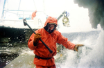 Crewman Jeff Newton braces as a wave splashes over the side of the crab fishing vessel {quote}Kiska Sea{quote} as it fishes for opilio crab in the Bering Sea in January and February of 1995.  Also known as freezing spray, waves and wet sea air slam into the boat freezing on impact causing ice to cover the boat.  Newton is carrying a sledgehammer which he is using to beat the ice off the sides of the boat.  Boats covered in ice become top heavy and are in danger of rolling over. The Bering Sea is known for having the worst storms in the world.  Crab fishing in the Bering Sea is considered to be one of the most dangerous jobs in the world.  This fishery is managed by the Alaska Department of Fish and Game and is a sustainable fishery.  The Discovery Channel produced a TV series called {quote}The Deadliest Catch{quote} which popularized this fishery.