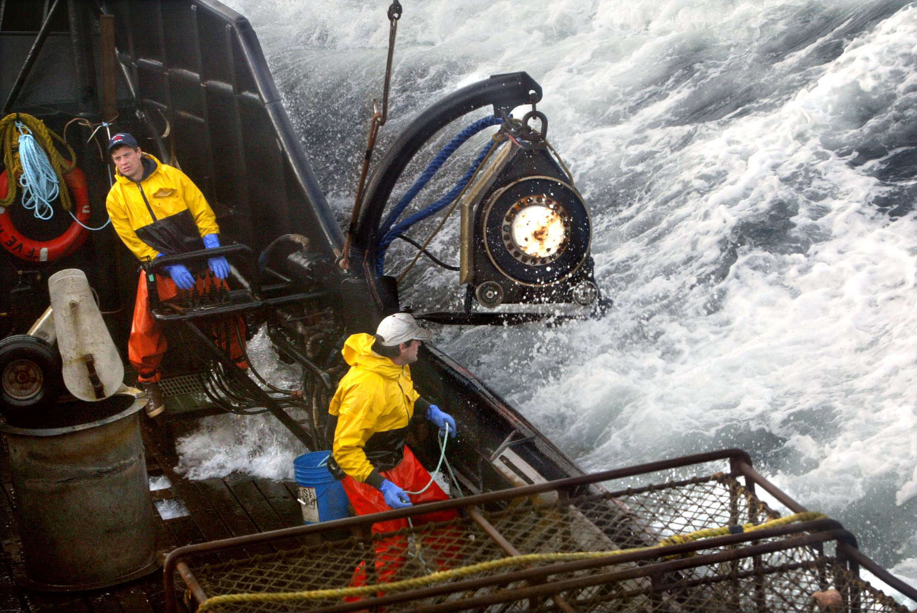 Crewman Lee Fleury prepares to throw the grappling hook at a crab pot buoy off in the distance while Lyndon Yockey (rear) runs the hydrolics to manuever heavy crab pots being stacked onboard. The 20003 Bristol Bay red king crab season lasted 5 days and 2 hours and was plagued with gale force winds of 35 knots or higher almost everyday causing to seas to rise 10 to 15 feet.