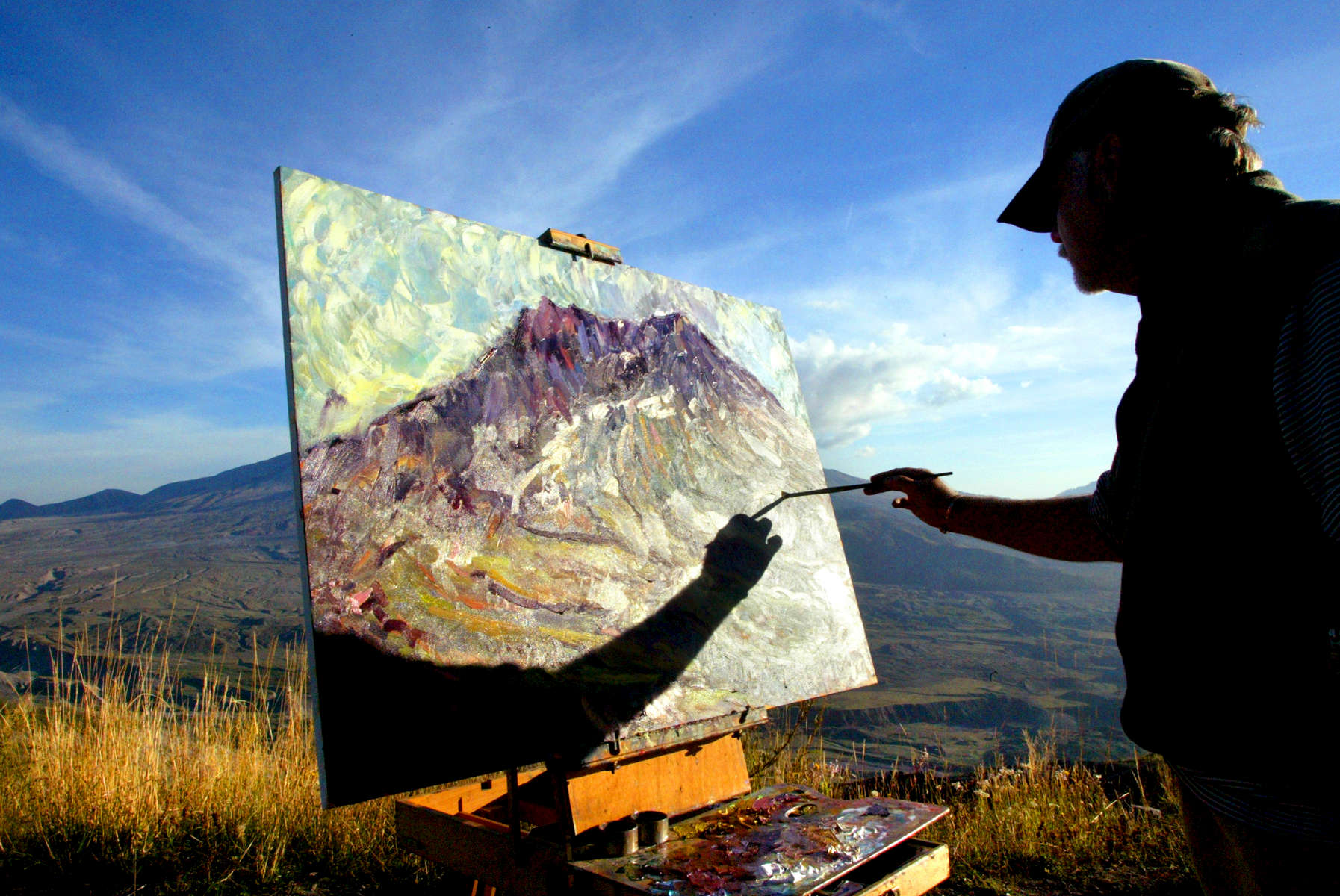 Roderick Smith from Portland, Oregon works on a painting he calls {quote}The Last Tango with Mount St. Helens{quote} outside the Johnston Hill Observatory in Washington on September 30, 2004. Active seismic activity has led scientists to believe the volcano could erupt any day. ...