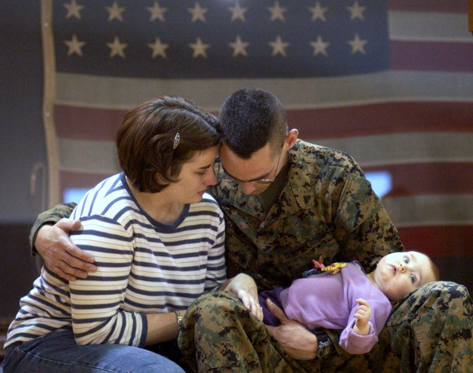 AMERICAN FAMILY::  Heidi and Aaron Conger with with 7-month-old daughter, Kennedy, spend a quiet moment together as families say goodbye during a farewell ceremony of Detachment Communications Company Headquarters Battalion 4th MARDIV at the Hessler Naval Armory in Indianapolis, Ind. Aaron will head to Wright Patterson Air Force Base in Dayton, Ohio, and then to an undisclosed location in support of Operation Enduring Freedom.